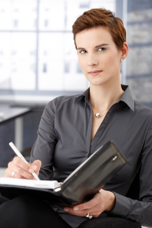 Portrait of businesswoman sitting in office, taking notes, looking at camera. Stock Photo - 8553243