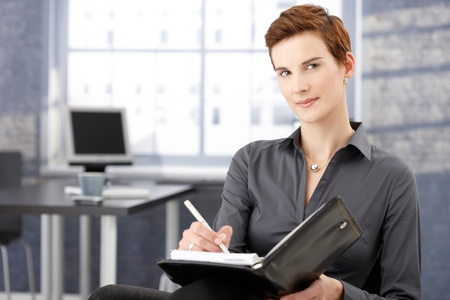 Smiling businesswoman writing notes in office, looking at camera, smiling. photo