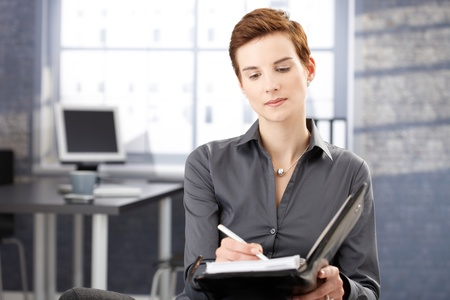 Businesswoman at work concentrating on taking notes. photo