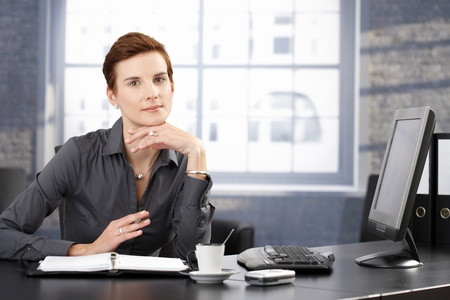 Smiling businesswoman sitting at desk in office, having coffee, working with organizer. Stock Photo - 8557569