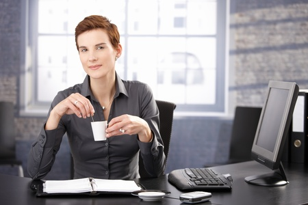 Businesswoman sitting at desk having coffee break, smiling at camera.