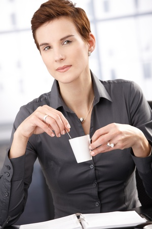 Businesswoman having coffee, with cup handheld, smiling at camera. photo