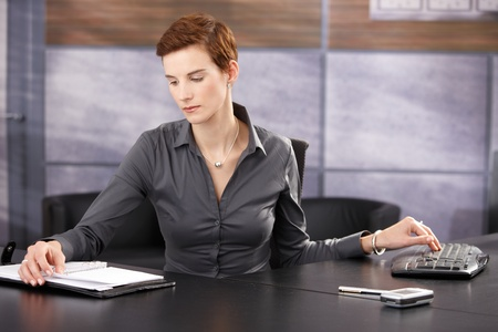 Businesswoman busy working, reviewing documents, typing on keyboard. photo