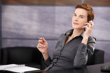 Confident businesswoman sitting at desk with pen handheld, concentrating on mobile phone call, smiling. Stock Photo - 8557575