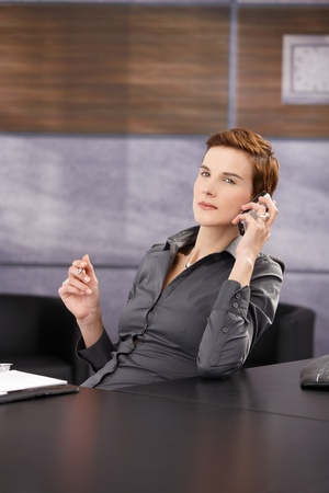 Portrait of serious businesswoman focusing on mobile phone call at desk in office. photo