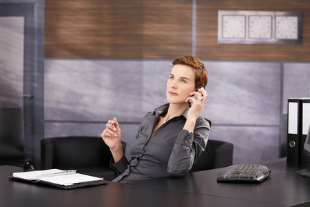 Elegant businesswoman sitting at desk, concentrating on work phone call with pen in hand. photo