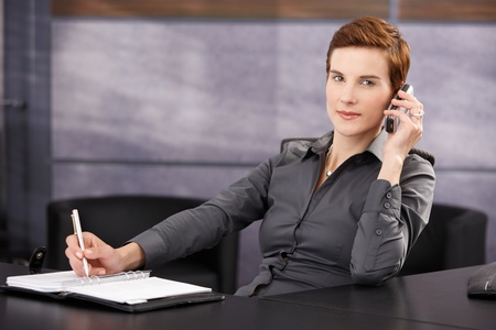 Businesswoman taking notes while on phone call, sitting at desk, smiling at camera. photo