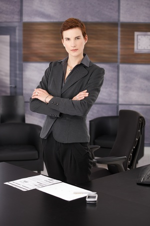 Trendy young businesswoman standing by meeting table at work, with folded arms, looking at camera. photo