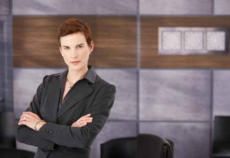 Portrait of determined young businesswoman in smart suit standing with arms folded in office, copyspace. photo