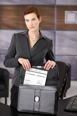 Serious businesswoman taking out document from briefcase, standing at desk in office, looking at camera. photo