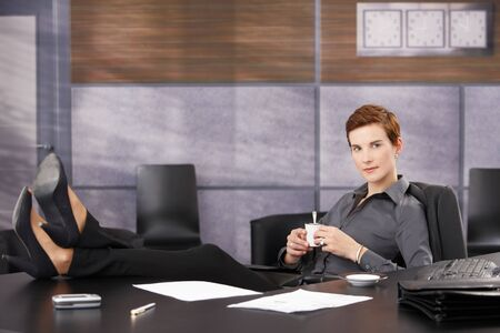 Cool businesswoman on coffee break sitting at desk with feet on table, wearing high heels, smiling at camera. photo