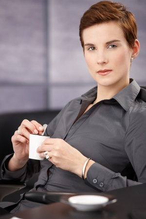 Portrait of serious businesswoman having coffee, holding cup, looking at camera. Stock Photo - 8558002