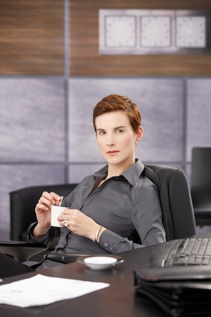 Confident trendy businesswoman drinking coffee at desk, looking at camera. Stock Photo - 8553301