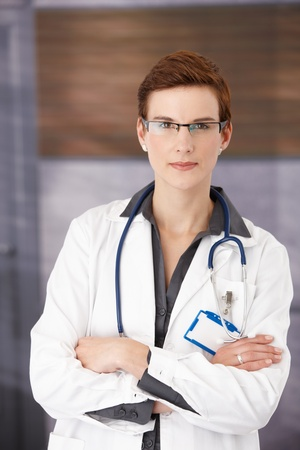 eye doctor: Young confident medical doctor standing in office in uniform with arms folded, smiling at camera Stock Photo