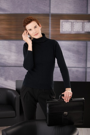 Trendy businesswoman standing in office with briefcase in hand, taking mobile call, smiling at camera. photo