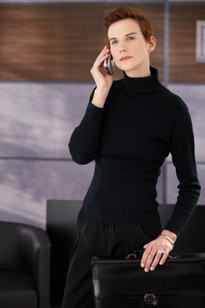 Elegant businesswoman standing in office, holding briefcase and concentrating on mobile phone call. photo