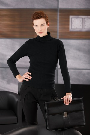Stylish businesswoman posing in office, standing with briefcase, looking at camera. photo