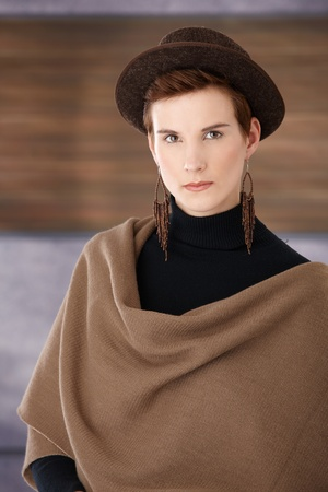 Trendy young woman wearing hat, big scarf and earring. photo