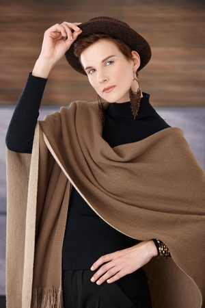 Trendy woman posing in fashionable accessory, hat, scarf and jewelry, looking at camera. photo