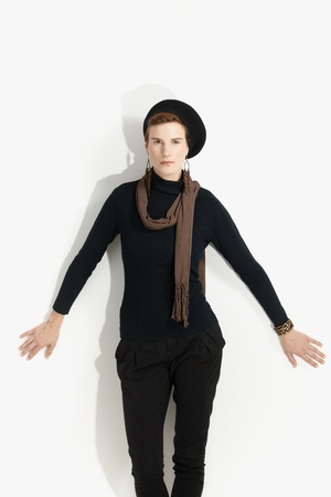 outspreading: Fashion portrait of young woman standing at wall with arms open, wearing trendy clothes.