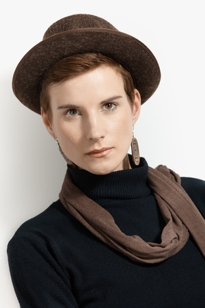Closeup fashion portrait of young woman wearing trendy hat and scarf, looking at camera confidently. photo