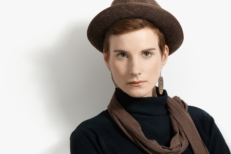 Hip young woman wearing earring and scarf posing in hat, looking at camera, Stock Photo - 8553298