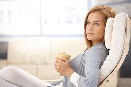 woman relaxing: Portrait of beautiful young woman drinking tea in armchair, smiling. Stock Photo
