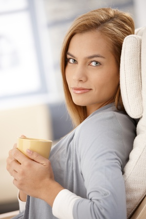 handheld: Portrait of smiling woman sitting with coffee cup handheld, looking at camera. Stock Photo