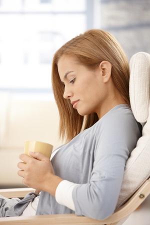 donna pensiero: Giovane donna pensando holding tazza di t�, seduti in poltrona, guardando verso il basso.