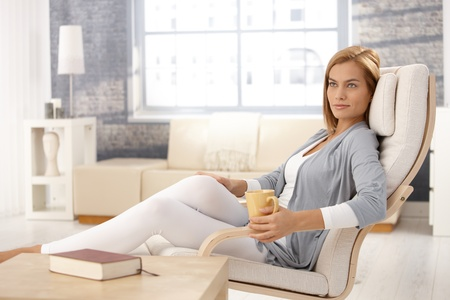 tea cosy: Portrait of attractive woman sitting in armchair with coffee mug, relaxing in living room, smiling.