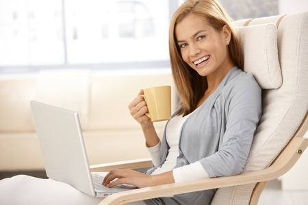 women holding cup: Happy young woman sitting in armchair with laptop computer, holding coffee mug, laughing, looking at camera. Stock Photo