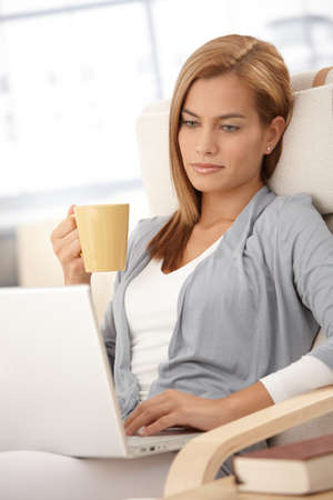 Young woman using laptop computer at home, holding tea cup, looking at screen, thinking. photo