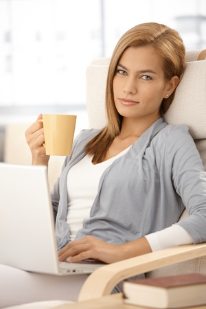 Attractive woman having coffee and using laptop computer at home, sitting in armchair, looking at camera, smiling. photo