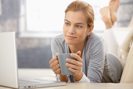 Portrait of daydreaming beauty looking at laptop computer screen, holding coffee mug, smiling. photo