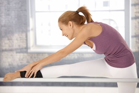 Happy ballerina stretching at bar, laughing at ballet class in exercise room. photo