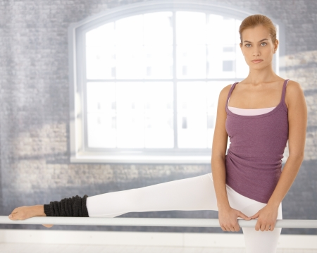 Girl doing ballet exercise, stretching, concentrating, standing at bar in ballet classroom. photo