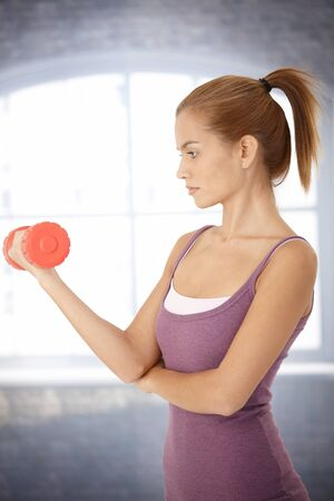 Sporty woman exercising with dumbbell, concentrating. Stock Photo - 8585440