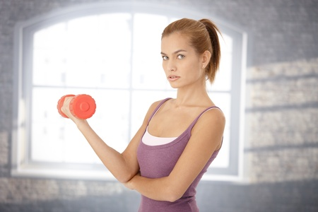 Portrait of young woman exercising with dumbbell, looking at camera. Stock Photo - 8579599
