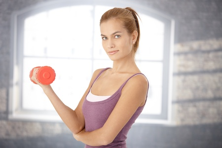 Smiling sporty woman doing exercise with dumbbell, looking at camera. photo