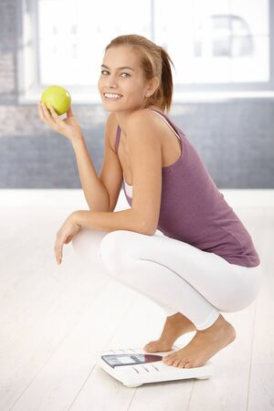 Portrait of happy squatter girl on scale holding green Apple, laughing at camera. Stock Photo - 8579610