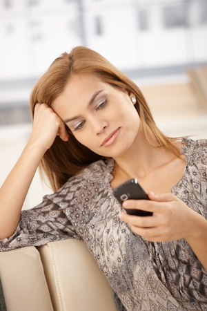 Pretty woman using mobile phone at home, smiling on couch. photo