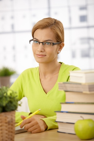University student girl wearing glasses sitting at desk with pile of books holding pen, smiling. Stock Photo - 8579731