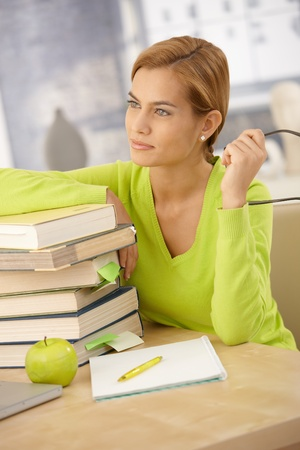 College girl smiling and thinking, sitting at desk with pile of books at home, holding glasses. photo