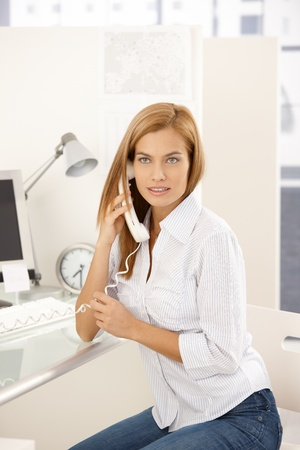 Office worker woman speaking on landline phone, sitting at desk in bright office, smiling. photo