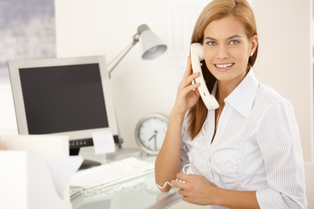 executive assistants: Happy office girl on landline phone call, sitting at desk, smiling at camera.