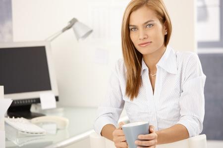 Office worker girl enjoying coffee break sitting at desk in bright office. Stock Photo - 8579607