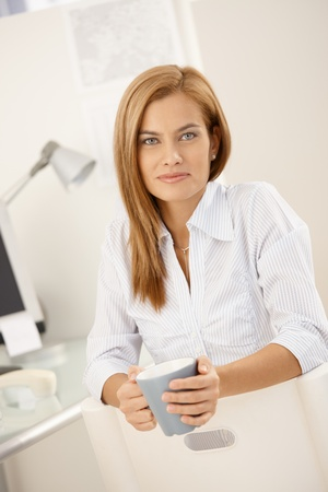 Smiling office worker woman having tea at desk, looking at camera. photo