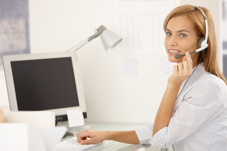 Happy call center worker girl sitting at desk in office, using desktop computer with headset, smiling. Stock Photo - 8586840