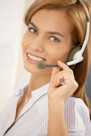 Closeup facial portrait of confident and attractive call center girl wearing headset, smiling at camera. photo