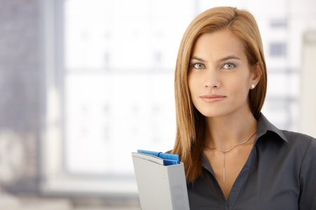 Portrait of attractive businesswoman in office with folders, looking at camera Stock Photo - 8586839